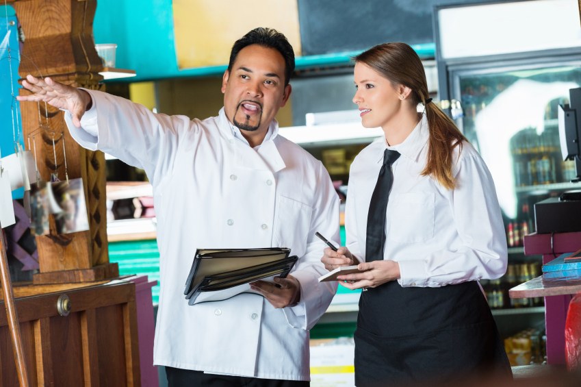 Millenial server training with chef in a restaurant