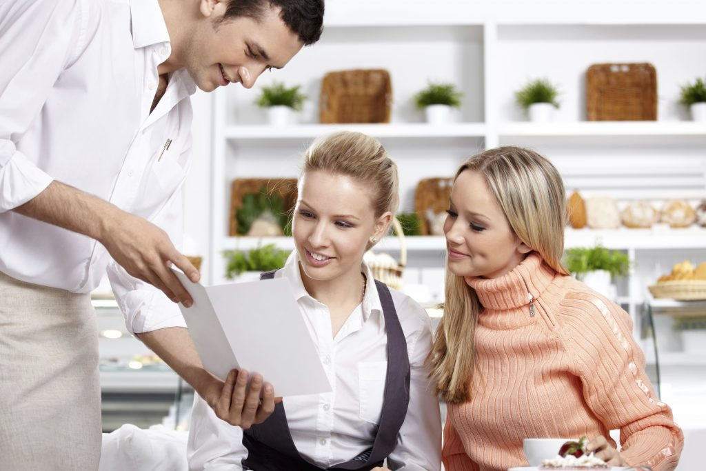 The young waiter shows the menu to two girls